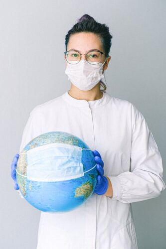 photo of person wearing protective wear while holding globe